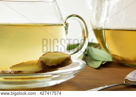 Detail Of Cup With Ginger Infusion On Wooden Table With Spoon And Leaves. Front View.