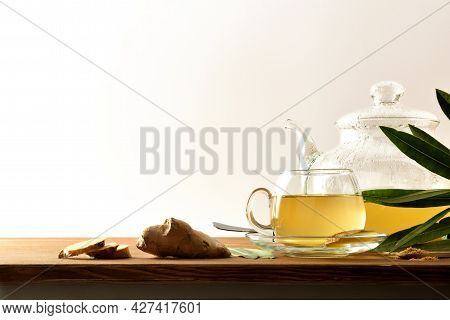 Hot Ginger-infused Mug On A Bench And  Teapot, Ginger Root And Leaves With White Isolated Background
