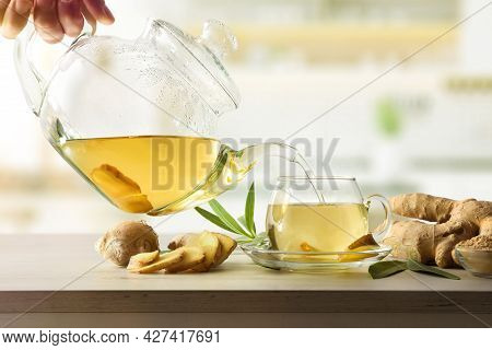 Man Serving Cup With Ginger Root Infusion On Kitchen Bench With Root And Slices. Front View.