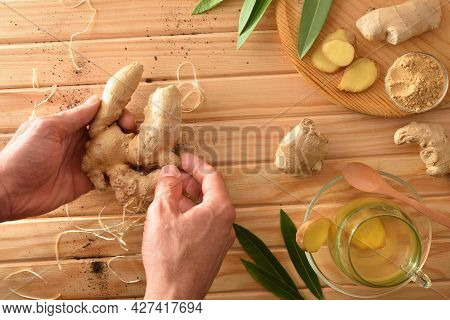 Organic Ginger Infusion On Wooden Table In The Countryside And Hands With Roots Ginger. Top View.