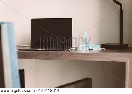New Normal Laptop Computer And Medical Mask On Table In Hotel Room.