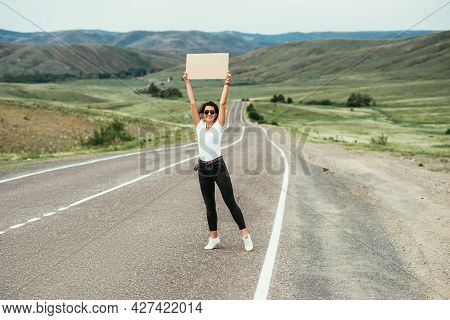 The Girl Is Hitchhiking. Passion For Travel, The Concept Of Auto Travel. A Hitchhiking Trip. A Woman