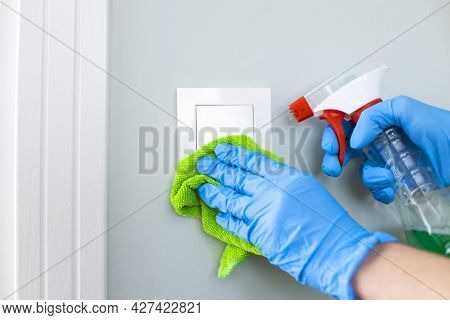 Woman Cleaning A Light Switch With A Disinfecting Spray