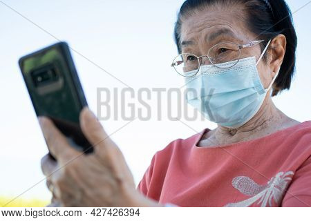Happy Asian Elderly Wearing A Face Mask And Answering A Video Call Using Her Smartphone In The Park