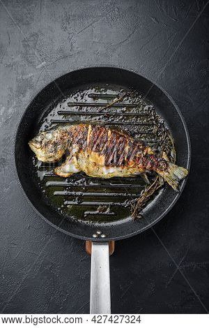 Grilled Sea Bream Or Dorado Raw Fish On Grill Hot Pan Over Textured Black Background,  Top View