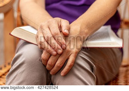 An Elderly Woman Holds A Bible On Her Lap And Prays After Reading The Bible
