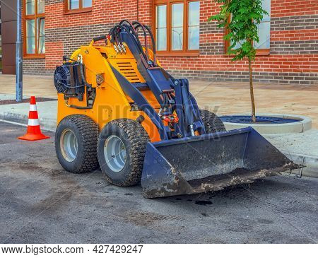 Dirty Midget Skid Loader Is Parked At The Construction Site. Small Bulldozer. Construction Machinery