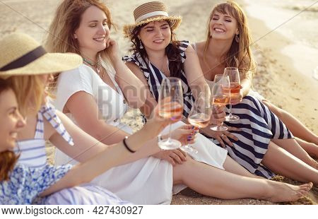 Happy Female Friends In Summer Dresses Smiling And Clinking Glasses Of Wine While Resting On Beach T