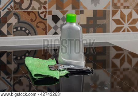 A Bottle Of Hob Cleaner, Cooker Cleaning Scraper And A Green Jay Cloth On A Cooker In A Kitchen. Cho