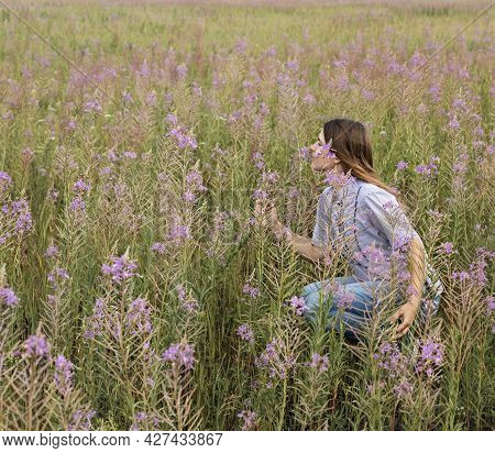 Beautiful Smiling Blond Young Woman In Light Purple Shirt Sitting On Field Of Fireweed Flowers Sniff