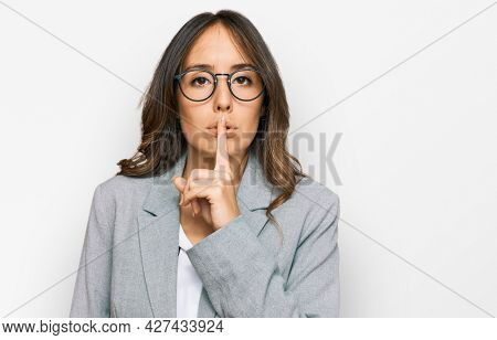 Young brunette woman wearing business clothes asking to be quiet with finger on lips. silence and secret concept.