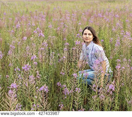 Young Beautiful Blond Woman In Purple Shirt Sitting In The Meadow Among Flowers Of Fireweed, Beauty