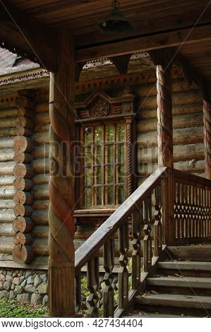 An Old Wooden Hut. Wooden Staircase, Porch, Window With Platbands. Architecture.
