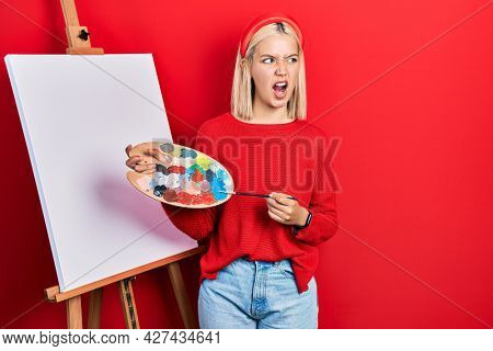 Beautiful blonde woman standing drawing with palette by painter easel stand angry and mad screaming frustrated and furious, shouting with anger. rage and aggressive concept.