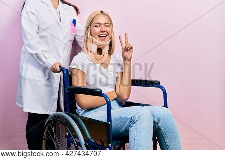 Beautiful blonde woman sitting on wheelchair with collar neck smiling with happy face winking at the camera doing victory sign. number two.