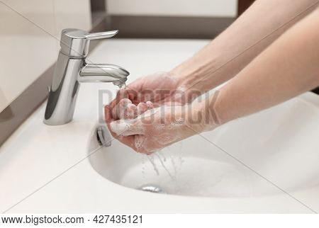 Hand Washing Concept. A Man Washes His Hands In The Bathroom With Antibacterial Soap. Personal Hygie