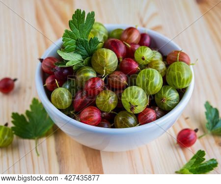 Red And Green Gooseberries In A Ceramic Bowl On A Light Wooden Background. Cooking Ingredients. Goos
