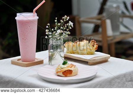 Bun ,bread Or Almond Bread Or Butter Bread And Strawberry Smoothie On The Table