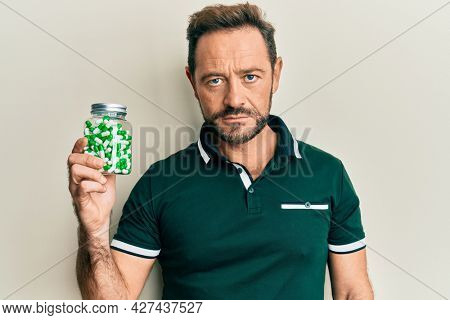 Middle age man holding pills thinking attitude and sober expression looking self confident