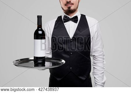 Unrecognizable Waiter In Elegant Uniform With Bow Tie Carrying Tray With Bottle Of Red Wine While Se