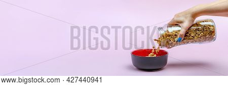 Muesli On A Pink Background. Pour Dry Muesli Flakes By Hand Into A Bowl. Pouring Muesli From A Glass