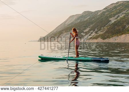 June 25, 2021. Anapa, Russia. Sporty Girls Float On Stand Up Paddle Board At Quiet Sea In Evening. W