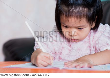 Adorable Girl Holding Pencil With Light Hand. Child Writing On The Book Intentionally. Kid Aged 4-5