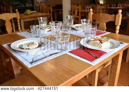 View Of Restaurant With Tables And Chairs. Main Table With Summer Dishes, Salad, Goat Roll Salad, Sa