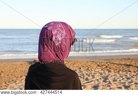 Young Woman With Headscarf Dressed In Traditional Arab Clothing By The Sea Waiting For Her Husband T