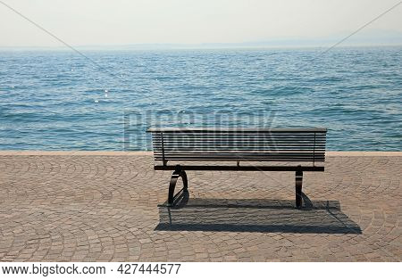Bench On The Shore With The Placid Water Symbol Of Tranquility And Relaxation Without People