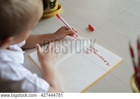 Happy Left-handed Boy Writing In The Paper Book With His Left Hand, International Left-hander Day Ce