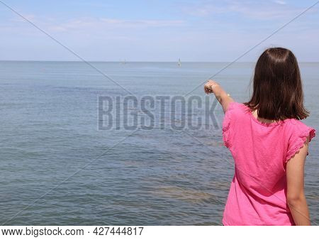 Young Girls With Magenta Colored Shirt Indicating A Point On The Horizon Of The Sea