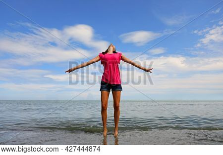 Caucasian Girl With Head Back And Arms Outstretched Comes To The Sea Happy And Excited About Life