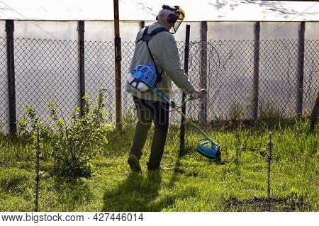 Gardener Takes Care Of Garden. Process Of Cutting Green Grass With Trimmer In Garden. Gasoline Power