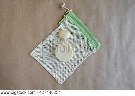 Round Natural Handmade Soap On Mesh Packaging Bag And Souvenir Stone Heart On Craft Paper. Hygiene,