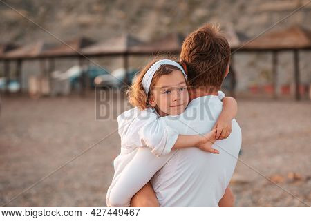Father's Day. Father Embracing His Daughter In Arms. Back View. Outdoor. Concept Of Happy Fatherhood