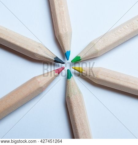 Colorful Wooden Pencils Arranged In A Symmetrical Radial Star Shape, Seen From Above. White Backgrou