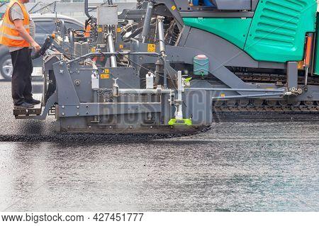 A Road Worker In An Orange Vest Operates An Asphalt Paver And Places Asphalt On A Bitumen Pavement W