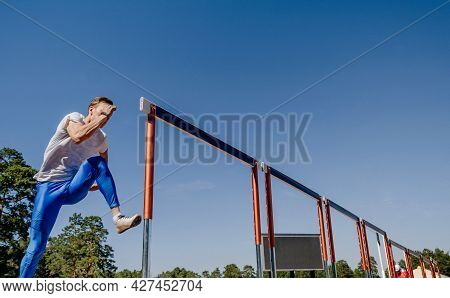 Male Athlete Run Hurdles At Athletics Competition