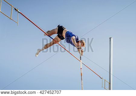 Male Athlete Pole Vault On Blue Sky Background