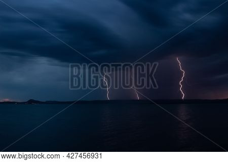 Multiple Bright Lightning Strikes The Lake Shore During A Thunderstorm. Strong Electrical Storm At N