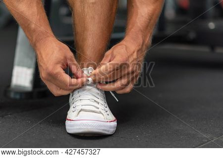 Sport Man Tying His Shoelaces Before A Workout In A Gym.cropped Image.preparing For Workout. Cropped
