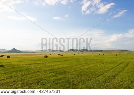 Summer Landscape With Hay Bales On Farming Green Fields Against The Background Of Cloudy Sky And Rid