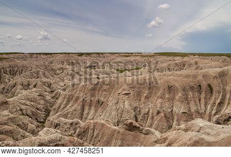 Badlands National Park, Sd, Usa - June 1, 2008: Wide Landscape Of Beige-brown Mountains Of Geologica
