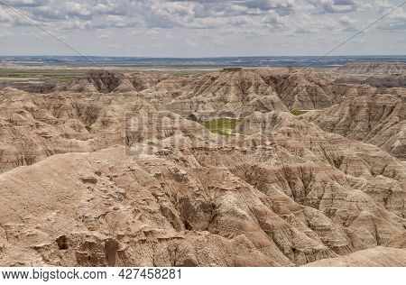 Badlands National Park, Sd, Usa - June 1, 2008: Wide Landscape With Mountains Cut By Red Lines Over