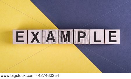 Word Example On Wooden Cubes On Yellow - Gray Background.