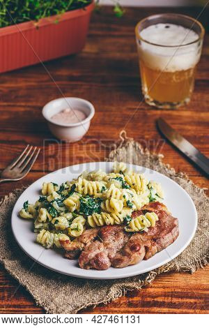 Pork Neck Steak With Creamy Spinach Pasta Garnished With Grated Parmesan Cheese On White Plate