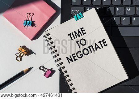 Notebook With Tools And Notes About Time To Negotiate Lies On Laptop.