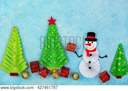 Christmas And New Year Greeting Card, Cut And Folded From Paper. Christmas Trees, Snowman With Gift.