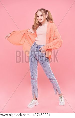 Teenage style. Full length portrait of a pretty teenage girl in bright summer clothes and with ponytails smiling at camera. Pink background.